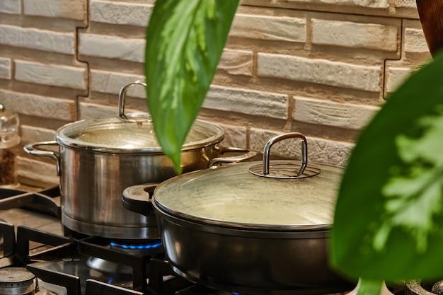 부엌에서 요리하는 동안 냄비와 프라이팬이 가스 스토브에 서 있습니다.