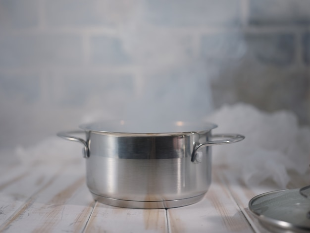 A saucepan of boiling water on a white table
