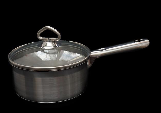 黒の背景にハンドル、カバー付きのステンレス鋼製の鍋。