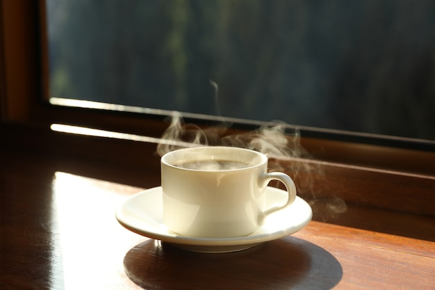 Saucer with cup of hot drink on wooden windowsill