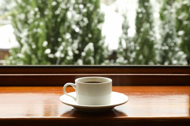 雪の天気の背景に対して木製の窓辺にカップとソーサー