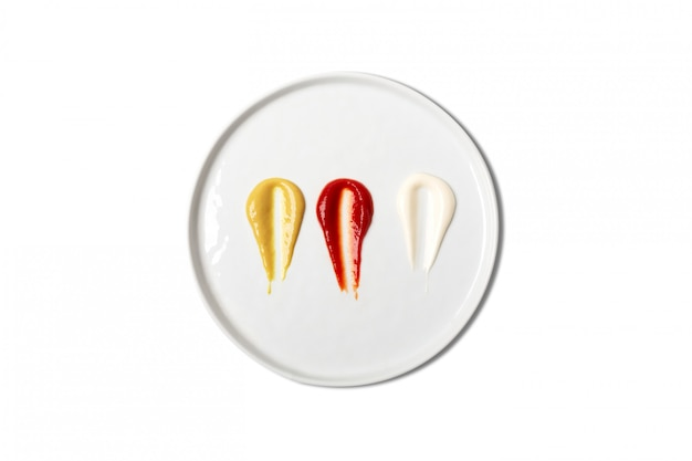 Sauces, including ketchup, mustard mayonnaise on white plate