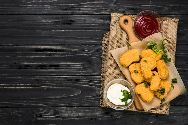 Sauces near cutting board with nuggets