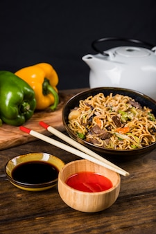 Sauces and thai fried noodles with chopsticks on wooden table