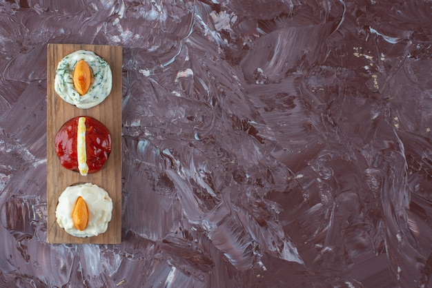 Sauces with chips on a board , on the marble table.