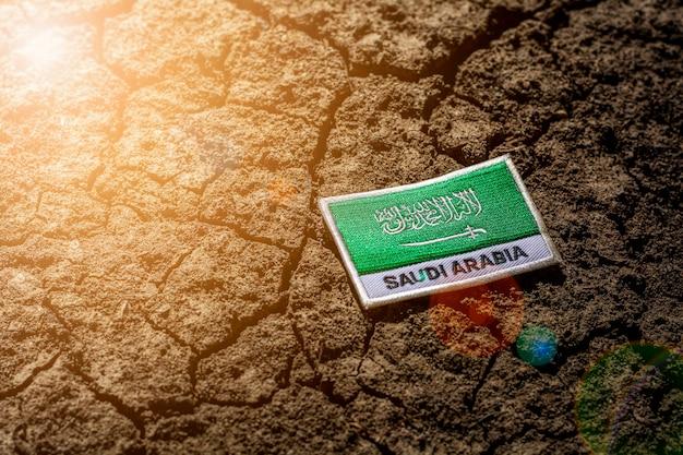 Saudi arabia flag on abandoned cracked ground.