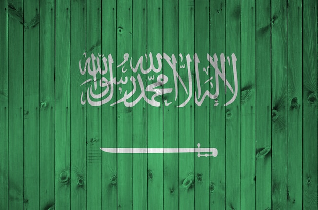 Saudi arabia flag depicted in bright paint colors on old wooden wall.