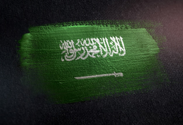 Saudi arabia flag made of metallic brush paint on grunge dark wall