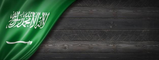 검은 나무 벽에 사우디 아라비아 플래그입니다. 파노라마.