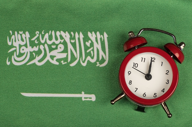Saudi arabia flag and vintage alarm clock close up. green flag with sword