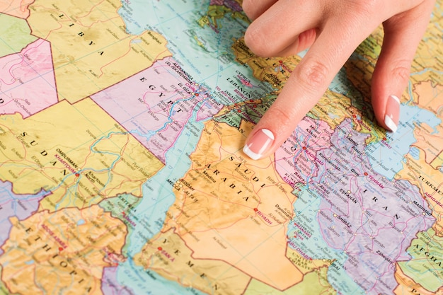 世界地図上のサウジアラビア。地図を指している女性の指。東の国を勉強しています。地域の最大の州。