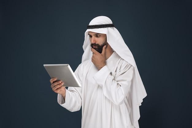 Uomo d'affari dell'arabia saudita sulla parete blu scuro