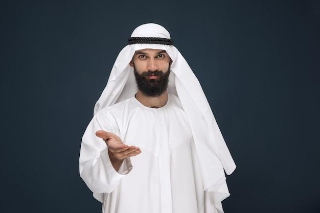 진한 파란색 벽에 사우디 아라비아 사업가