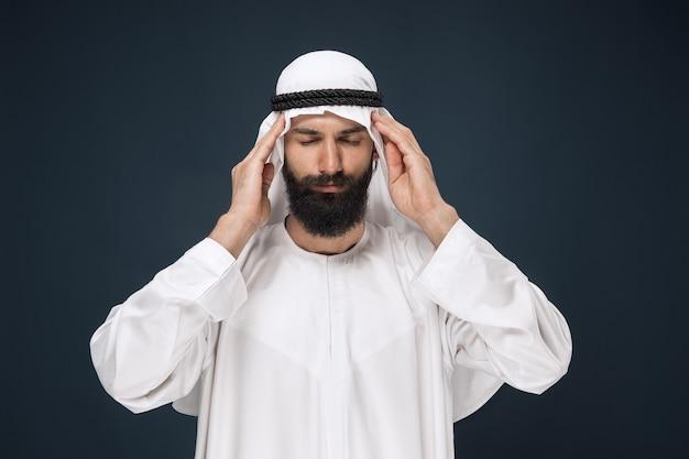 진한 파란색 벽에 사우디 아라비아 사람