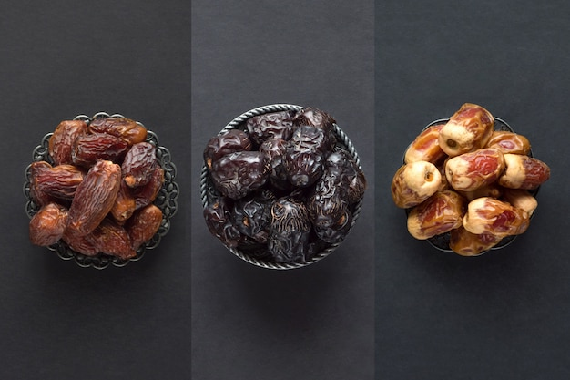 Saudi dates fruits are laid out on a dark table.