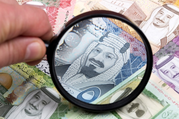 Saudi riyal in a magnifying glass