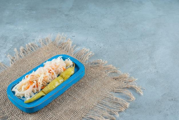 대리석 테이블에 질감에 나무 접시에 소금에 절인 양배추와 통조림된 고추.