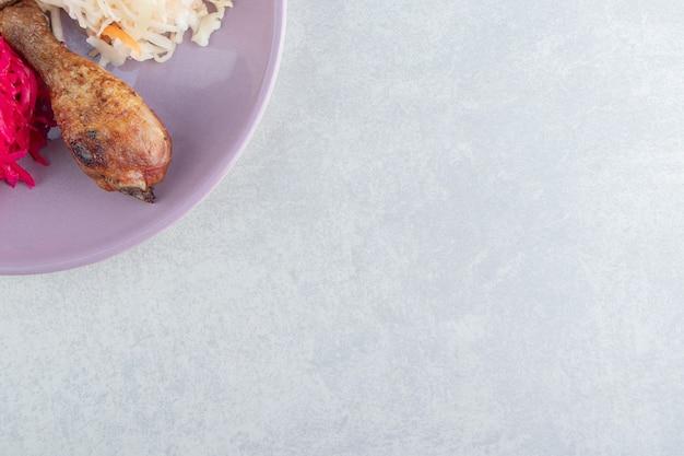 보라색 접시에 소금에 절인 양배추와 닭 다리입니다.