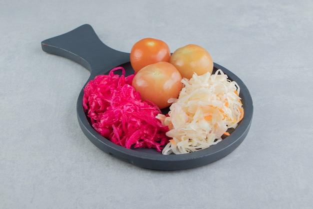 블랙 보드에 소금에 절인 양배추와 절인 토마토