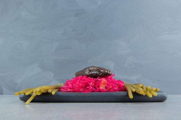 Квашеная капуста и маринованные баклажаны на черной доске