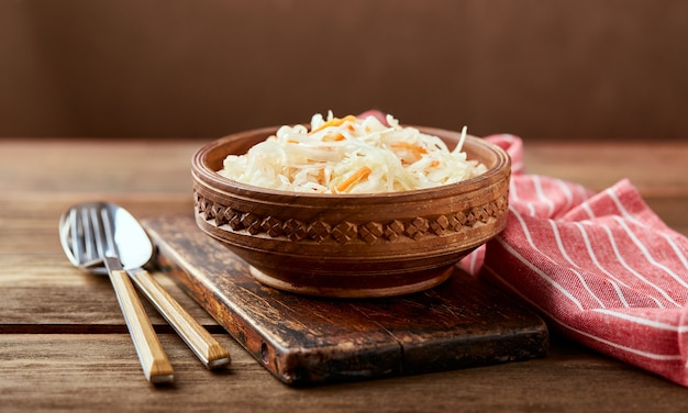Sauerkraut, fermented cabbage with carrots in bowl on wooden background. superfoods for support the immune system.
