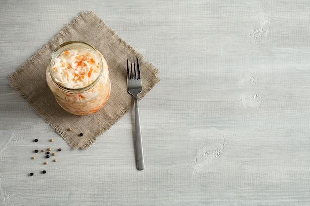 Квашеная капуста в стеклянной банке на холстовой салфетке, лежащей на деревянном белом