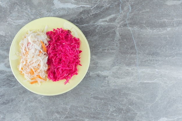 노란 접시에 소금에 절인 양배추입니다. 흰색과 분홍색.