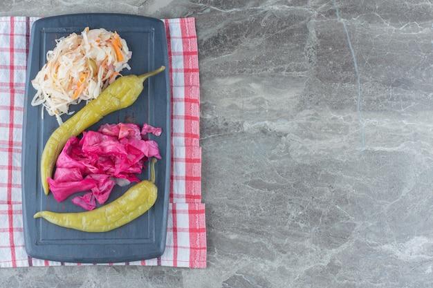Crauti e peperoni su tavola di legno grigia.
