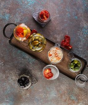 Квашеная капуста, маринованная морковь, маринованные огурцы, маринованные оливки и оливки, сушеные помидоры в стеклянных банках