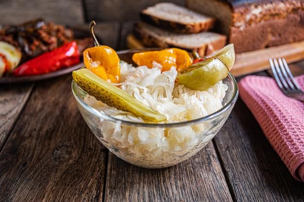 나무 테이블에 있는 유리 그릇에 소금에 절인 양배추 토마토 오이와 후추 홈메이드 피클
