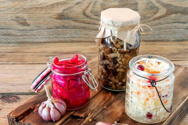 소금에 절인 양배추 다양한 보존 항아리. 나무 테이블에 사탕무를 곁들인 당근과 샐러드 양배추를 곁들인 홈메이드 사우어크라우트. 발효 식품.