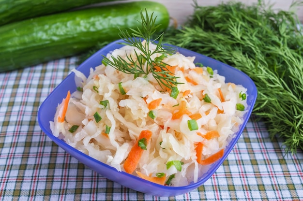 Sauerkraut with carrot and greens in a blue bowl. dietary dish. lenten meal.