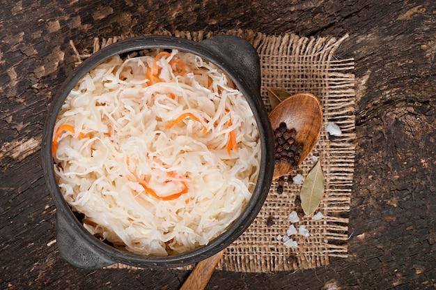 Квашеная капуста с морковью в деревянной миске