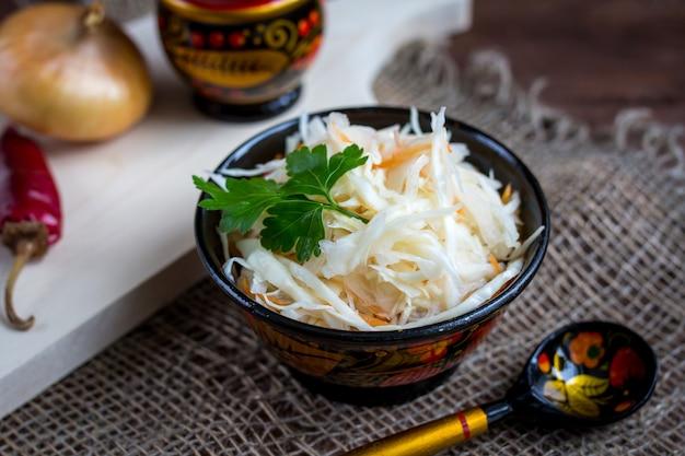 Sauerkraut with carrot in wooden bowl