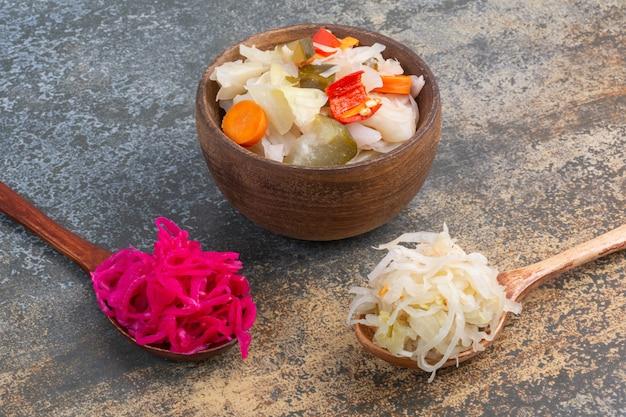 Sauerkrauts on spoon and bowl.