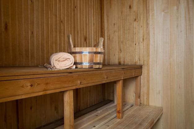 Сауна, банные принадлежности. деревянное ведро и полотенце