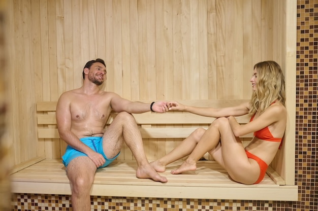 Sauna. a couple looing relaxed while spending time in sauna together