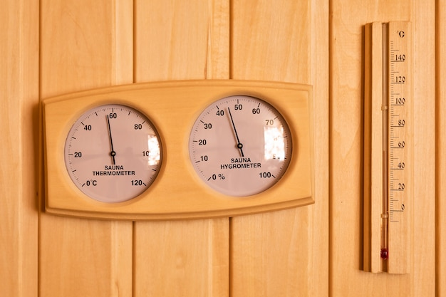 나무 벽에 사우나 온도계 및 습도계 온도 섭씨