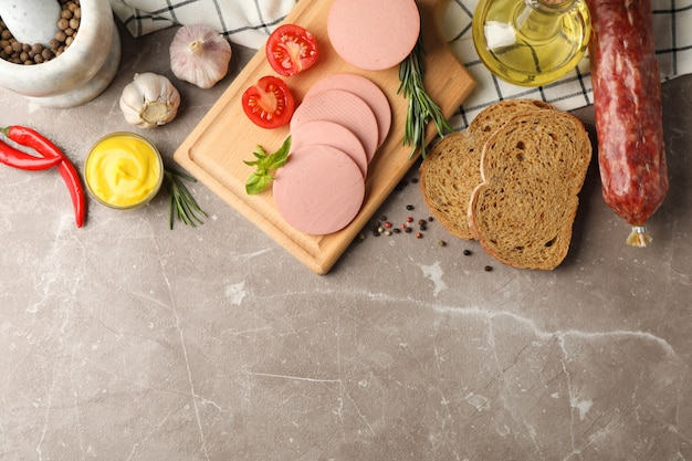 Колбаса, хлеб, специи, полотенце и доска на сером фоне, место для текста
