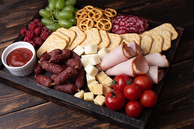 暗い木製の背景にソーセージ、チーズ、フルーツのシャルキュトリーボード。