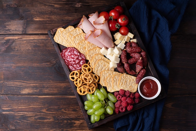 暗い木製の背景、クローズアップの豚肉ボード上のソーセージ、クラッカー、フルーツ、チーズ。