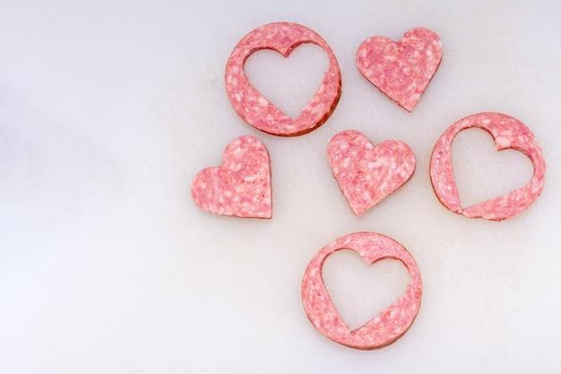 白いキッチンボード、上面図、クローズアップでハートの形にカットされたソーセージ。バレンタインデーの料理