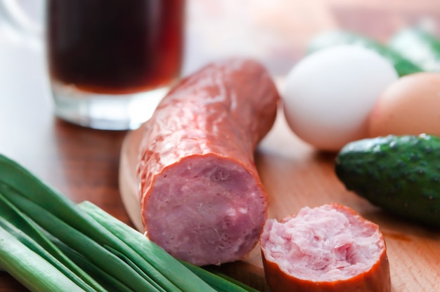 Sausage in the foreground with green onions, cucumber and eggs on a blurred background.