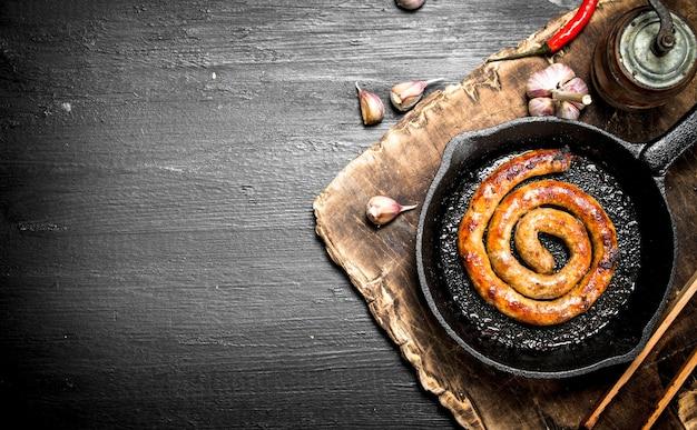 Колбаса на сковороде с чесноком и специями на черной доске.