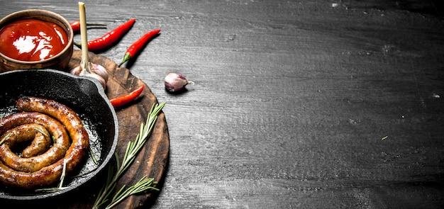 Колбаса на сковороде с острым томатным соусом на черной доске