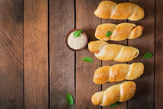 Колбаса в тесте, посыпанная кунжутом на деревянном столе в деревенском стиле