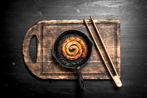 Колбаса в сковороде на черной доске.
