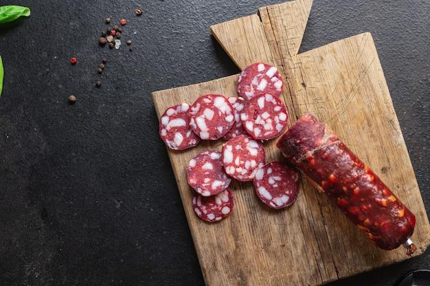 Колбаса с кусочками бекона говяжья или свинина копченая или вяленая закуска на столе