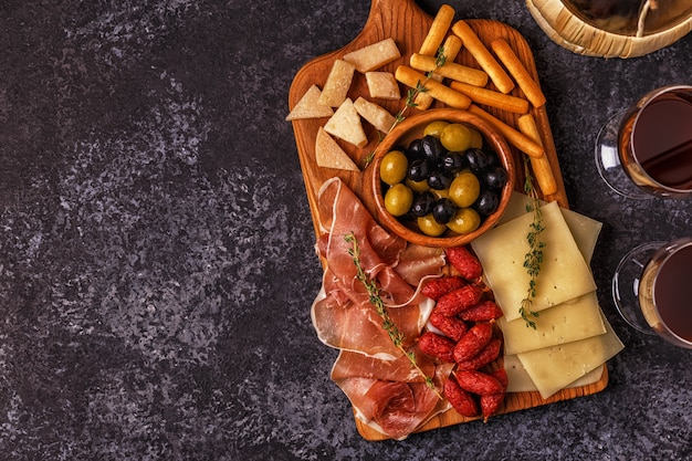 Sausage, olives, prosciutto, cheese and bread sticks on cutting board and wine