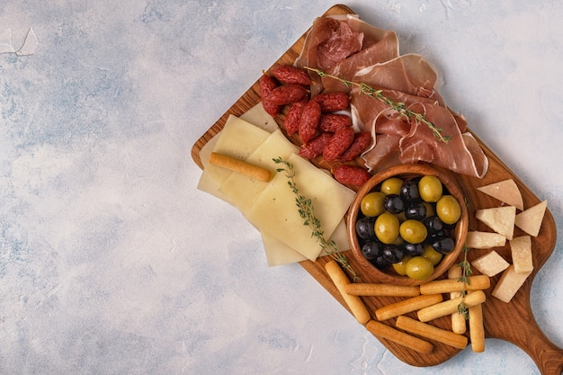 Sausage, olives, prosciutto, cheese and bread sticks on cutting board